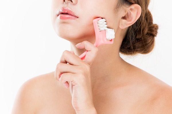 美顔器を使う女性 顔のリフトアップ