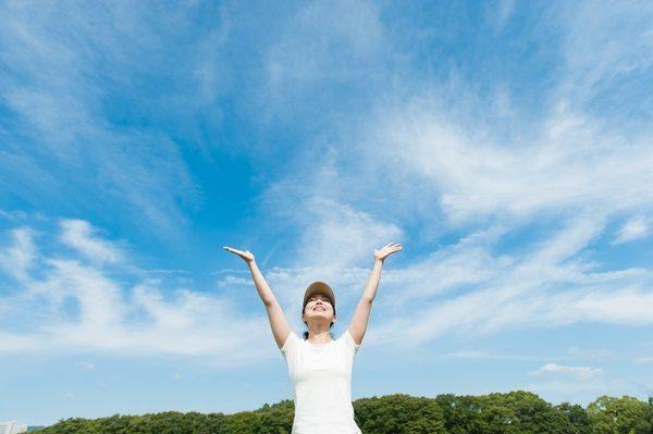 空に向かって手を広げる女性 黒にんにく