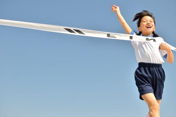 運動会 青空で走る女の子(体操服、ゴールテープ)