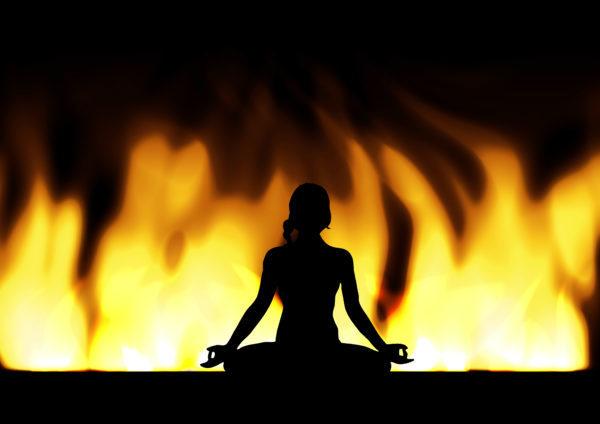 気功・ヨガ・瞑想する女性シルエットと炎の背景