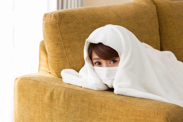 マスク・毛布を被る女性